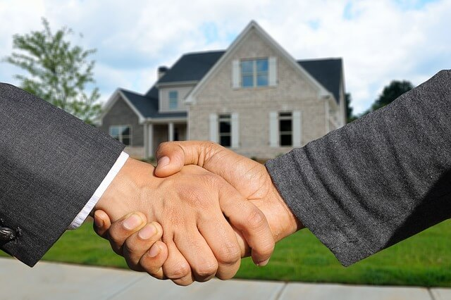 Shaking hands infront of a sold house
