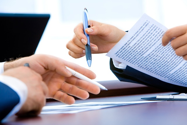 hands with a pens and documents