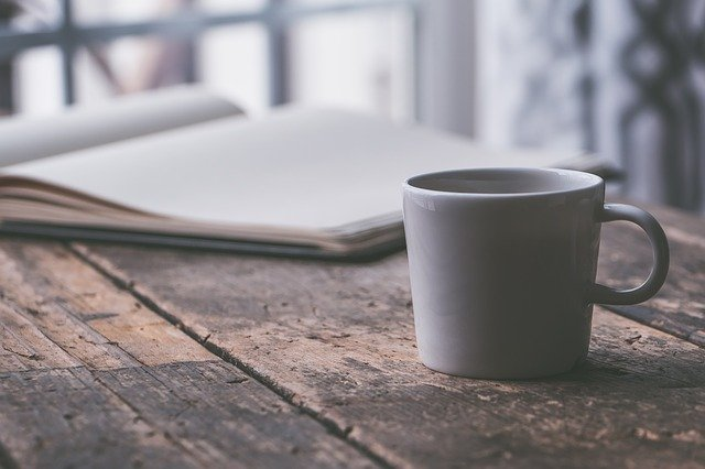 coffee cup and open book on a wooden table