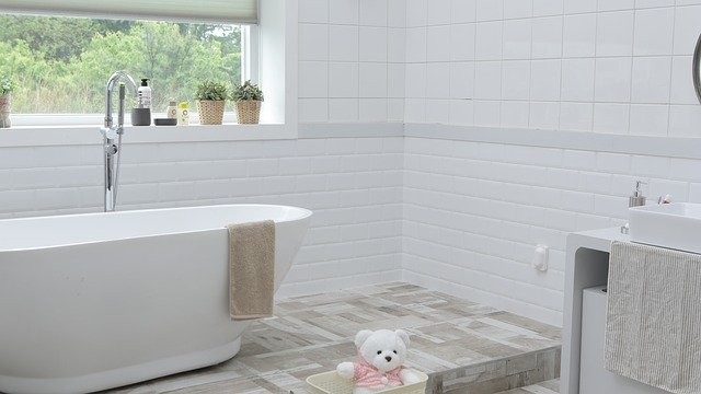 white bathroom featuring white tiles, a white bath tub, and a white teddy bear